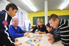 Junge Migranten in der deutschen Schule, die zusammen spielt Lizenzfreie Stockfotos