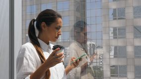 Junge Mischrasse-Geschäftsfrau Drinking Coffee und mit Handy im Büro nahe großem Fenster mit Stadt-Ansicht an stock footage