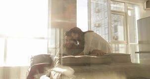 Junge Mischrasse-Paar-glücklicher hispanischer Mann Sit On Coach Asian Woman, der zusammen Zellintelligentes Telefon-Morgen-Sonne stock video footage