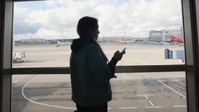 Junge Mischrasse-touristische Frau, die Handy nahe Fenster am Abfahrt-Flughafenabfertigungsgebäude verwendet 4K stock video