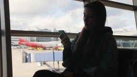 Junge Mischrasse-touristische Frau, die Handy nahe Fenster am Abfahrt-Flughafenabfertigungsgebäude verwendet 4K stock footage