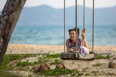 Junge Mischrassefrau liegt auf dem Schwingen auf dem Seestrand relax stockbild