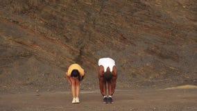 Junge Mischrassepaare, welche die Übung im Freien auf dem entsteinten Strand tun Sexy Brunettefrau, die mit persönlicher Eignung  stock video footage