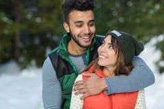 Junge-Mischungs-Rennpaar-Schnee Forest Outdoor Winter Walk Stockfotos