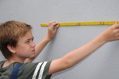Junge misst die Wand mithilfe eines Zollstocks stockbild