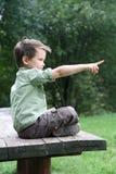 Junge mit überkreuzten Beinen auf einer hölzernen Bank Stockbilder