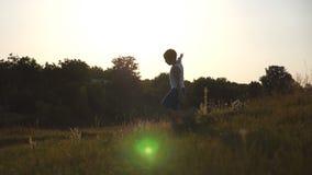 Junge mit angehoben, wie Flugzeug Betrieb auf grünem Gras am Feld am sonnigen Tag übergibt Kind, das am Rasen rüttelt stock video footage
