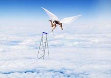 Junge mit Angel Wings-Fliegen, springend von der Treppe im Himmel Lizenzfreies Stockbild