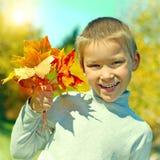 Junge mit Autumn Leafs stockbild