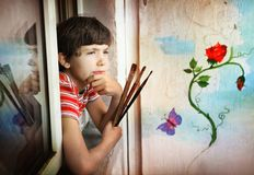 Junge mit Bürsten und seiner Malerei Lizenzfreies Stockfoto