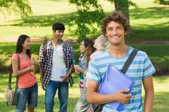 Junge mit Collegefreunden im Hintergrund am Campus stockfoto