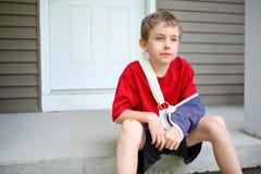 Junge mit dem Arm in einem Riemen lizenzfreie stockbilder