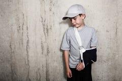 Junge mit dem Arm in einem Riemen von einem gebrochenen Humerus, der einen Baseball trägt stockfotos