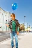 Junge mit dem blauen Fliegenballon, der auf Straße steht Stockbild