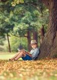 Junge mit dem Buch, das unter großem Baum im Park sitzt Lizenzfreies Stockfoto