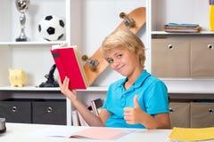 Junge mit dem Daumen, der oben Hausarbeit tut und ein Buch liest Lizenzfreies Stockfoto
