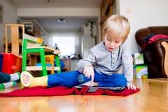 Junge mit dem gebrochenen Bein in der Form, die auf Tablette spielt Stockbild