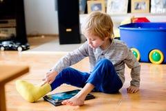 Junge mit dem gebrochenen Bein in der Form, die auf Tablette spielt Stockfotos