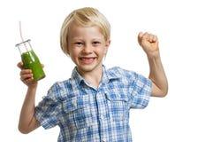 Junge mit dem grünen Smoothie, der Muskeln biegt stockbild