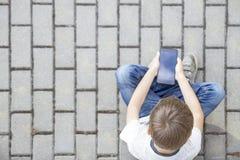 Junge mit dem Handy, der auf der Pflasterung sitzt Ablesen, Anwendungen spielend oder mit Beschneidungspfad eingeschlossen Getren stockfoto