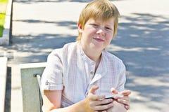 Junge mit dem Handy, der auf einer Bank sitzt Lizenzfreie Stockfotos