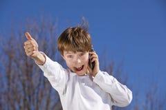 Junge mit dem Handy, der oben Daumen aufwirft Stockbilder