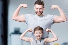 Junge mit dem jungen Mann, seinem Trainer oder Vater, die Muskeln zeigen lizenzfreie stockfotos
