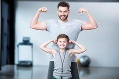 Junge mit dem jungen Mann, seinem Trainer oder Vater, die Muskeln zeigen lizenzfreie stockbilder