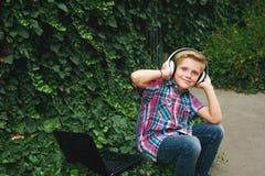 Junge mit dem Laptop und Kopfhörern, zum draußen zu tun Lizenzfreies Stockfoto