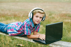 Junge mit dem Laptop und Kopfhörern, zum draußen zu tun Stockfotografie