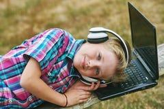 Junge mit dem Laptop und Kopfhörern, zum draußen zu tun Stockbild