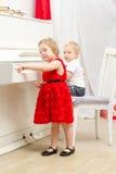 Junge mit dem Mädchen, das nahe weißem Klavier sitzt Lizenzfreies Stockbild