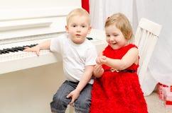 Junge mit dem Mädchen, das nahe weißem Klavier sitzt stockbild