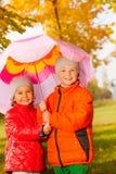 Junge mit dem Mädchen, das Regenschirm und Stand zusammenhält Stockfotos