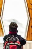 Junge mit dem Rucksack, der heraus das Fenster schaut Lizenzfreie Stockfotografie