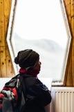 Junge mit dem Rucksack, der heraus das Fenster und das Denken schaut Lizenzfreies Stockfoto