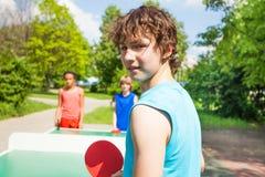 Junge mit dem Schläger, der gedreht wird und Tischtennis gespielt ist Lizenzfreie Stockfotografie