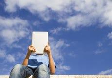 Junge mit dem Tablet-PC, der gegen blauen Himmel sitzt Niedrige Winkelsicht Leute, Technologie, Bildung, Freizeitkonzept Stockbild
