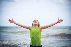Junge mit den angehobenen Händen auf der Küste Stockfotos