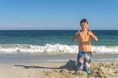 Junge mit den Daumen oben am Strand Lizenzfreies Stockfoto