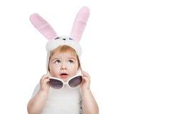 Junge mit den großen blauen Augen, die in den Osterhasenohren gekleidet werden, entfernen Sonnenbrille und oben schauen Stockbild
