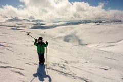Junge mit den Wanderstöcken, die in den Bergen wandern Lizenzfreie Stockfotografie