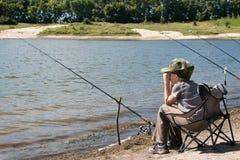 Junge mit der Angelrute, die auf dem Ufer des Teichs sitzt Stockbild