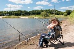 Junge mit der Angelrute, die auf dem Ufer des Teichs sitzt stockfotografie