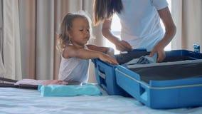 Junge mit der kleinen Tochter, die zusammen einen Koffer sammelt stockfoto