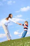 Junge mit der Mutter, die am Hintergrund des blauen Himmels spielt Stockfotos