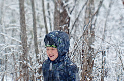Junge mit der Schaufel, die im Schneewald spielt Stockbild