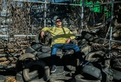 Junge mit der städtischen Ausstattung, die auf einem Berg von alten Reifen sitzt stockbilder