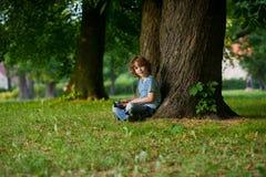 Junge mit der Tablette auf einem Schoss Lizenzfreies Stockfoto