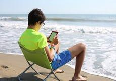 Junge mit ebook und kurze Hosen auf dem Strand Lizenzfreie Stockbilder